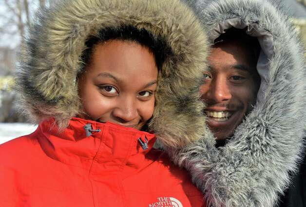 Rosea Martinez and her husband, Jose Montanez, of Albany manage a smile from behind big fur collars during a cold walk home along Madison Ave. Tuesday Jan. 7, 2013, in Albany,NY.  (John Carl D'Annibale / Times Union) Photo: John Carl D'Annibale / 00025268A