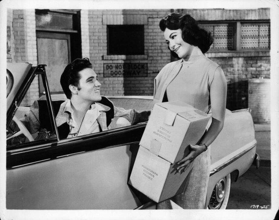 Elvis Presley sitting in the driver's seat of a convertible car smiling at Judy Tyler as she smiles back in a scene from the film 'Jailhouse Rock', 1957. (Photo by Metro-Goldwyn-Mayer/Getty Images) (Getty Images)