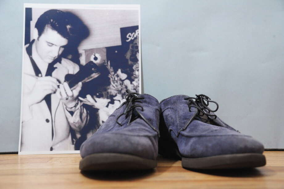 An autographed pair of Elvis Presley's original blue suede shoes and a photo of him autographing them. (Photo by Michael Loccisano/Getty Images) (Getty Images)