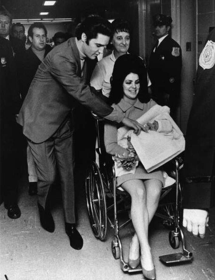 Singer Elvis Presley (1935 - 1977), then 33, and his 22 year-old wife Priscilla, leaving the Baptist Hospital, Memphis, Tennessee, with their baby daughter Lisa-Marie, born on February 2nd. (Photo by Keystone/Getty Images) (Getty Images)