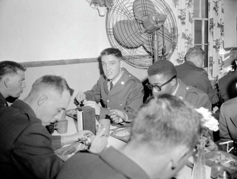 Pvt. Elvis Presley puts away a meal of fried fish and french fries after his arrival at Fort Hood on March 28, 1958, to begin eight weeks of basic military training in the 2nd Armored Division. Photo: ASSOCIATED PRESS FILE PHOTO