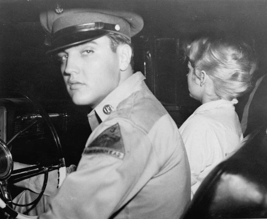 Pvt. Elvis Presley, accompanied by his girlfriend Anita Wood, prepared to drive from his home in Killeen, Texas to join his Army outfit at Ft. Hood, Texas late Friday night, September 21, 1958. The rock 'n roll singer is being transferred to Germany. Anita, who had been crying, refused to face the camera because she said she was red-eyed. (AP Photo) Photo: Anonymous, ASSOCIATED PRESS / AP1958