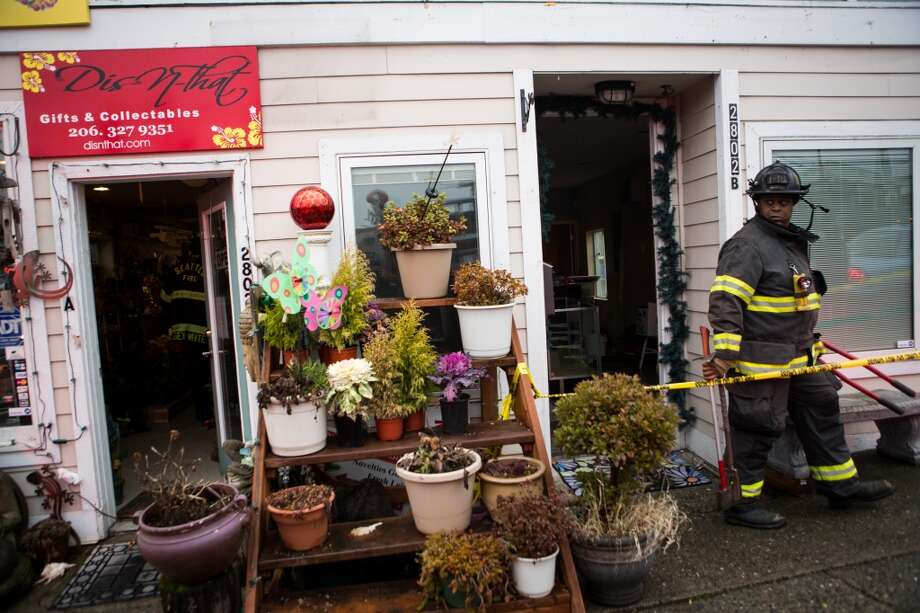 A firefighter exits a building after an explosion in an apartment in the back of the building shifted part of the building off its foundation on Tuesday, January 7, 2014 at the intersection of South McClellan Street and Martin Luther King Jr. Way South. Photo: JOSHUA TRUJILLO, SEATTLEPI.COM
