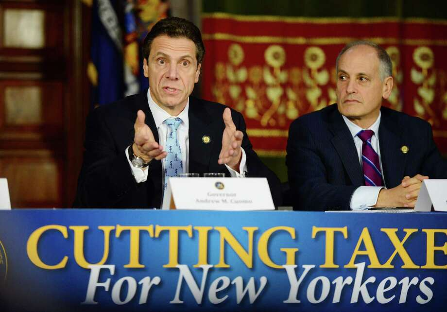 Gov. Andrew Cuomo, left, outlines his new tax reduction plan as Secretary to the Governor Larry Schwartz listens during a press conference Monday  at the Capitol. (Will Waldron/Times Union) Photo: WW