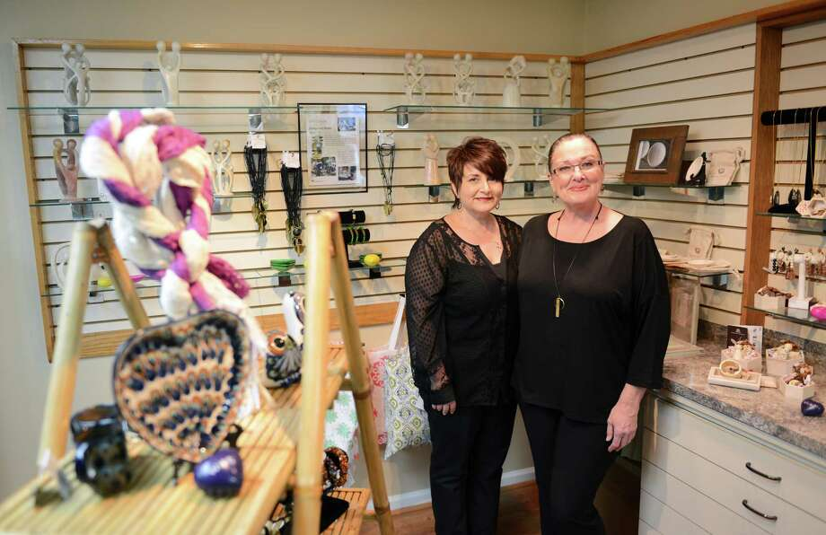 Owners Maria Rodrigues, left, and Robin Miller pose in the new boutique at Escape Salon and Spa in Bethel, Conn. on Tuesday, Jan. 7, 2014.  The shop sells items from fair-trade, eco-friendly companies, including unique items like purses made of bottle caps, bowls made from recycled chopsticks and waste paper ornaments. Photo: Tyler Sizemore / The News-Times