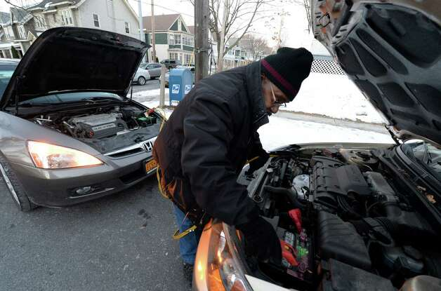 Charles Goodby gives his wife's car a jump in the early morning single digit cold Tuesday, Jan. 7, 2014, in Albany, N.Y.    (Skip Dickstein / Times Union) Photo: SKIP DICKSTEIN
