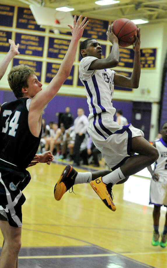 Westhill's Jeremiah Livingston leaps to shoot over the reaching Peter Ciaccio, of Wilton, during their basketball game at Westhill High School in Stamford, Conn., on Monday, Jan. 6, 2014. Westhill won, 51-43. Photo: Jason Rearick / Stamford Advocate