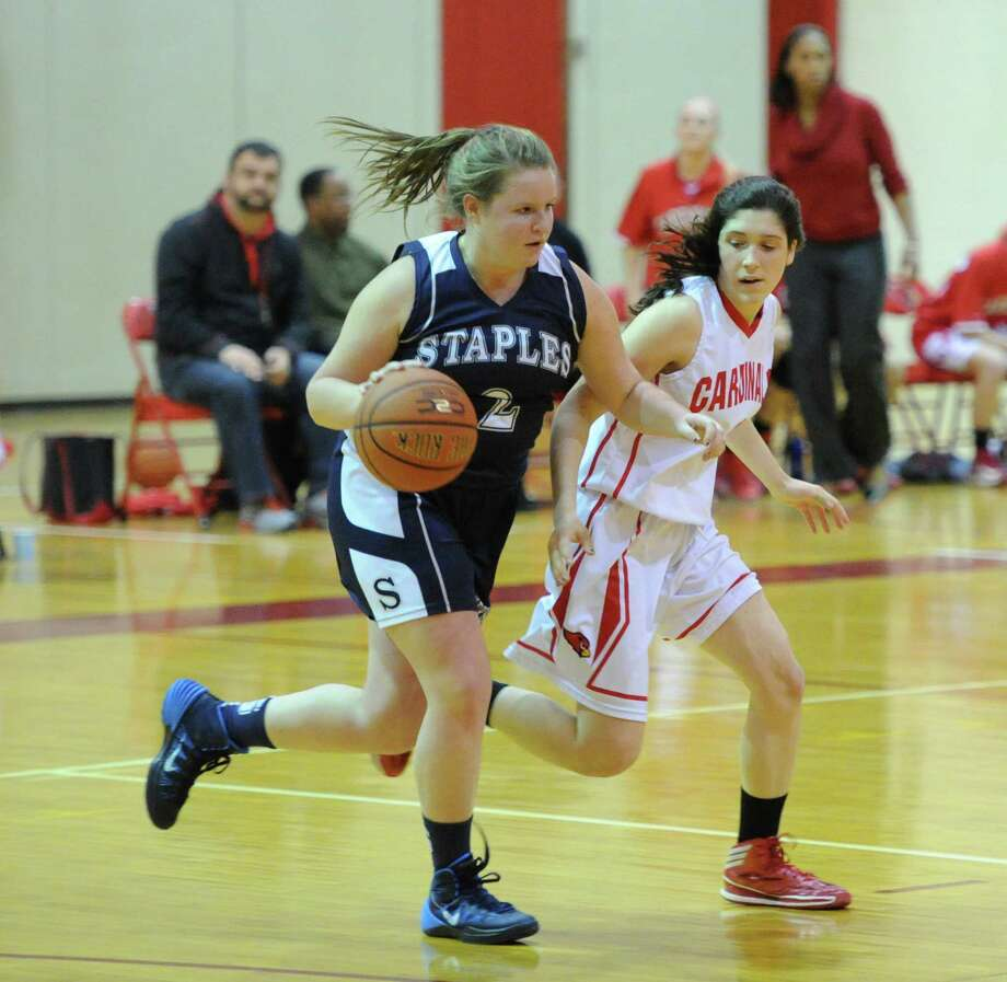 At left, Margaret Fair (#2) of Staples dribbles upcourt while being defended by Leigh Galletta (# 4) of Greenwich during the girls high school basketball game between Greenwich High School and Staples High School at Greenwich, Tuesday, Jan. 7, 2014. Photo: Bob Luckey / Greenwich Time