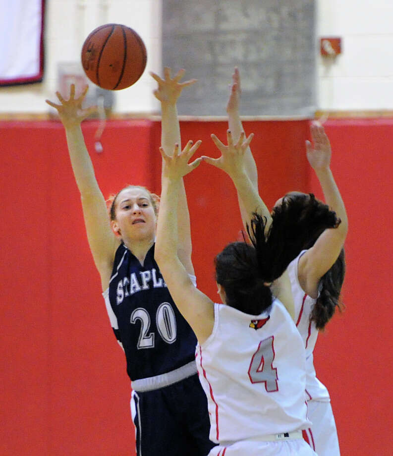 At left, Theresa Mall (#20) of Staples looks to pass while being defended by Leigh Galletta (#4) of Greenwich during the girls high school basketball game between Greenwich High School and Staples High School at Greenwich, Tuesday, Jan. 7, 2014. Photo: Bob Luckey / Greenwich Time