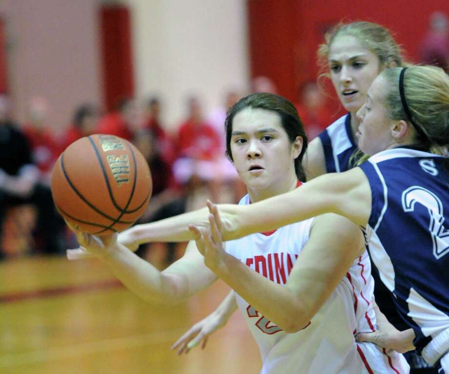 At left, Jamie Kockenmeister (# 23) of Greenwich passes the ball as Theresa Mall, right, of Staples, defends,during the girls high school basketball game between Greenwich High School and Staples High School at Greenwich, Tuesday, Jan. 7, 2014. Photo: Bob Luckey / Greenwich Time