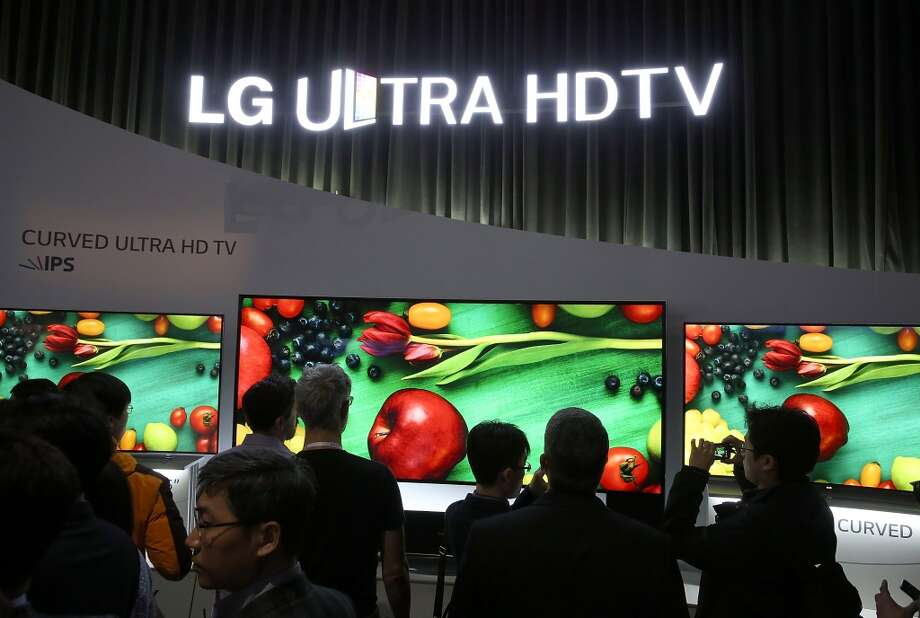 Attendees look at a display of curved Ultra HDTV televisions at the LG booth. LG announced this week it would sell an Ultra HD set as small as 49 inches diagonally, which could bring entry level prices closer to $2,000 for top brands. Photo: Justin Sullivan, Getty Images