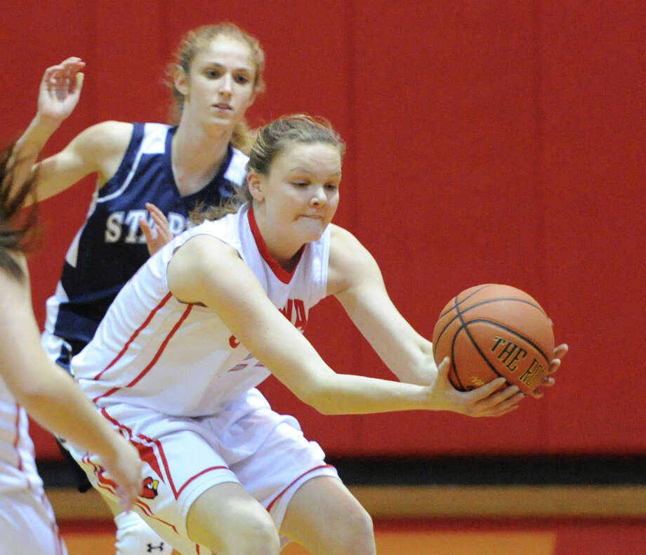 At right, Abby Wolf of Greenwich saves the ball from going out-of-bounds during the girls high school basketball game between Greenwich High School and Staples High School at Greenwich, Tuesday, Jan. 7, 2014. Photo: Bob Luckey / Greenwich Time