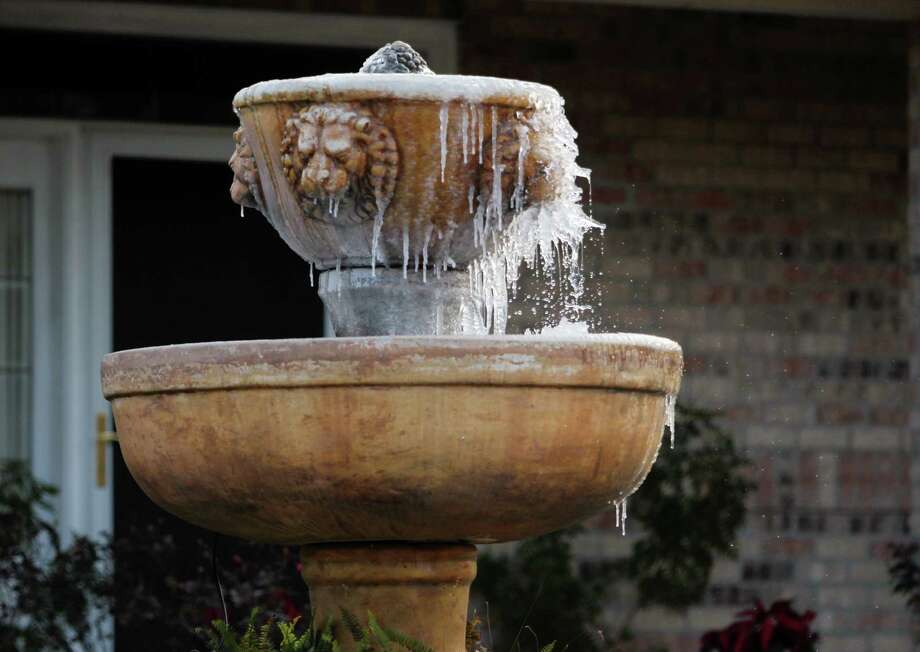 Icicles hang from a fountain in a front yard Tuesday, Jan. 7, 2014, in Lafayette, La. Bitter cold settled in around Louisiana overnight and into Tuesday morning. (AP Photo/The Lafayette Daily Advertiser, Leslie Westbrook)  NO SALES ORG XMIT: LALAF101 Photo: Leslie Westbrook / The Lafayette Daily Advertiser