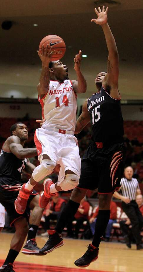Houston Cougars Tione Womack (14) goes up for a basket against Cincinnati Bearcats forward Jermaine Sanders (15) during the first half of a college basketball game at Hofheinz Pavilion, Tuesday, Jan. 7, 2014, in Houston. Photo: Karen Warren, Houston Chronicle / © 2013 Houston Chronicle
