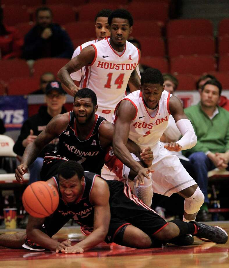 Cincinnati Bearcats forward Jermaine Sanders (15) reaches out for a loose ball with Cincinnati's Titus Rubles (2) and Houston Cougars forward Mikhail McLean (1) during the first half of a college basketball game at Hofheinz Pavilion, Tuesday, Jan. 7, 2014, in Houston. Photo: Karen Warren, Houston Chronicle / © 2013 Houston Chronicle
