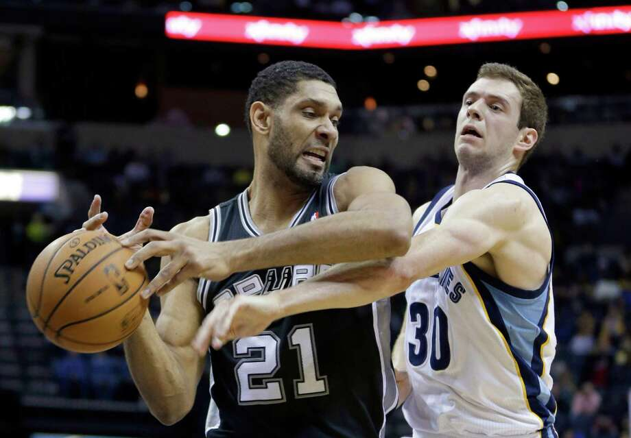 Memphis Grizzlies' Jon Leuer (30) hits the ball away from San Antonio Spurs' Tim Duncan (21), of U.S. Virgin Islands, in the first half of an NBA basketball game in Memphis, Tenn., Tuesday, Jan. 7, 2014. (AP Photo/Danny Johnston) Photo: Danny Johnston, Associated Press / AP