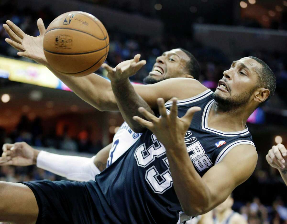 San Antonio Spurs' Boris Diaw (33), of France, gets a defensive rebound from Memphis Grizzlies' James Johnson in the first half of an NBA basketball game in Memphis, Tenn., Tuesday, Jan. 7, 2014. (AP Photo/Danny Johnston)