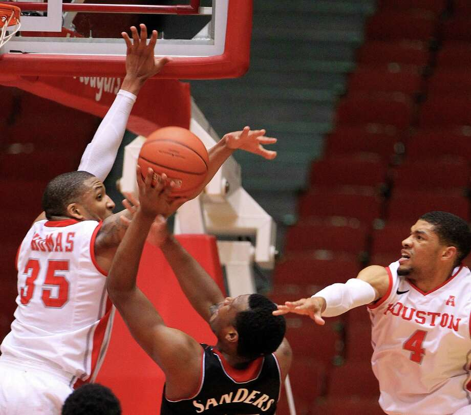 Cincinnati Bearcats forward Jermaine Sanders (15) goes up for a basket against Houston Cougars forward TaShawn Thomas (35) and guard LeRon Barnes (4) during the second half of a college basketball game at Hofheinz Pavilion, Tuesday, Jan. 7, 2014, in Houston. Photo: Karen Warren, Houston Chronicle / © 2013 Houston Chronicle