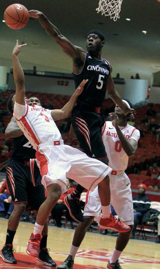 UH's Jaaron Simmons falls prey to the long arm of Cincinnati forward Justin Jackson (5). Photo: Karen Warren, MBI / Houston Chronicle