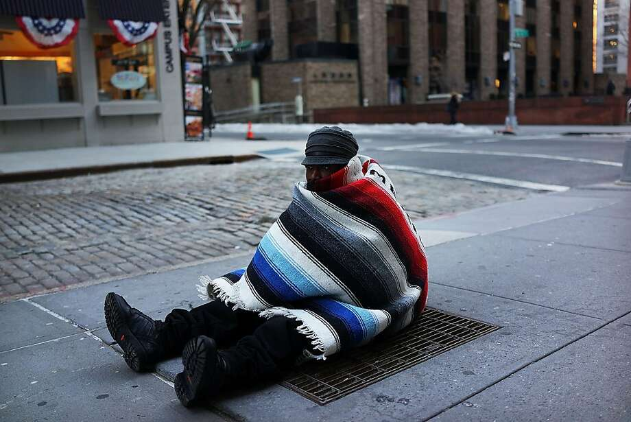 "NEW YORK, NY - JANUARY 07:  Prince, who is homeless, sits on a subway grate to keep warm on a frigid day on January 7, 2014 in New York, United States. A ""polar vortex"" carrying Arctic air and wind gusts of up to 50 mph has engulfed New York City and much of the Northeast making for life threatening weather conditions.  (Photo by Spencer Platt/Getty Images) Photo: Spencer Platt, Getty Images"