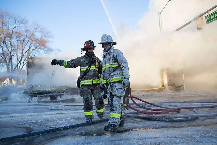 Ann Arbor firefighters covered in ice work to put out a fire that engulfed Happy's Pizza in Ann Arbor, Mich., on Tuesday, Jan. 7, 2014.   Firefighters worked for several hours in temperatures that dipped to 15 degrees below zero to extinguish a blaze at the pizza shop. No injuries were reported following the fire. (AP Photo/The Ann Arbor News, Courtney Sacco ) LOCAL TV OUT; LOCAL INTERNET OUT Photo: Courtney Sacco, Associated Press