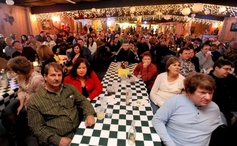 Customers gather at long tables to watch Chris Knight perform at Big Rich Courville's in Beaumont, Thursday, December 1, 2011. Tammy McKinley/The Enterprise