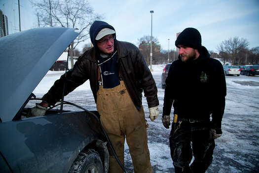 Travis Olesak (R) helps jump start Dan Couillard's (L) vehicle as temperatures remain in the negative digits on January 7, 2014 in Milwaukee, Wisconsin. A 'polar vortex' of frigid air centered on the North Pole dropped temperatures to the negative double digits at its worst. Photo: Darren Hauck, Getty Images / 2013 Getty Images