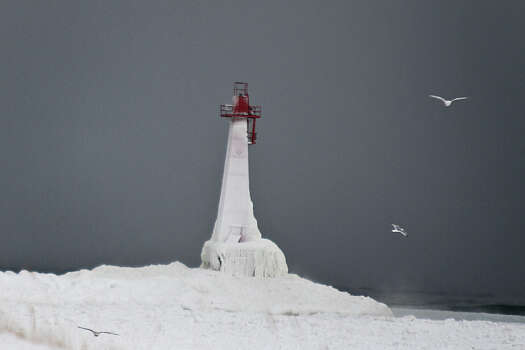 The lighthouse at Pere Marquette Beach is completely frozen after a severe winter storm hit Tuesday, Jan. 7, 2014 in Muskegon, Mich. The brutal polar air that has made the Midwest shiver over the past few days spread to the East and the Deep South on Tuesday, shattering records that in some cases had stood for more than a century. Photo: Madelyn P. Hastings, ASSOCIATED PRESS / AP2014