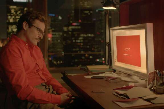 "Theodore (Joaquin Phoenix) develops an emotional connection with his computer operating system in ""Her."""
