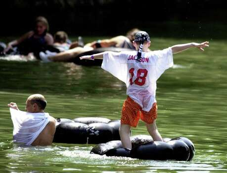 People cool off in the Guadalupe River during the Labor Day weekend Sunday, Sept. 3, 2000, in New Braunfels, Texas. Temperatures on the last day of summer reached over the century mark again, forcing people to cool off in any way they could. (AP Photo/Express-News, Kevin Geil). Photo: KEVIN GEIL, AP / EXPRESS-NEWS