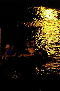 METRO   A couple of night tubers relax under the faint light from nearby park lighting on the Comal River Saturday night in New Braunfels.   NIGHT TUBING ON THE COMAL RIVER FROM TEXAS TUBES   TOM REEL/STAFF   JUNE 17, 2006. Photo: TOM REEL, SAN ANTONIO EXPRESS-NEWS / SAN ANTONIO EXPRESS-NEWS