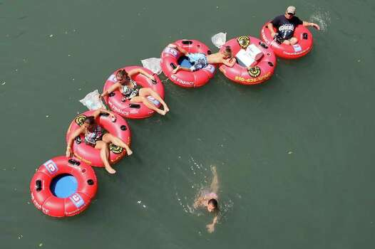 A tuber takes to swimming while riding the Comal River on Labor Day weekend, Sunday, Sept. 4, 2011. Crowds were lower than expected over the holiday weekend according to the New Braunfels Police Department. Photo: JERRY LARA, Jerry Lara/Express-News / SAN ANTONIO EXPRESS-NEWS