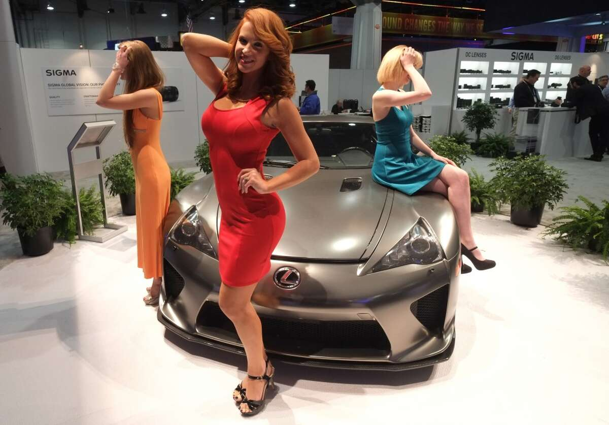 Models pose for pictures at the booth of Sigma America during the 2014 International CES.