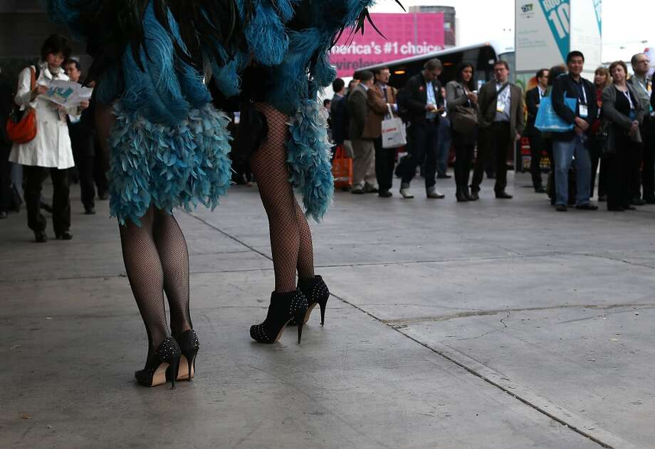 Attendees waiting in line for shuttle buses watch two women dressed as showgirls. Photo: Getty Images
