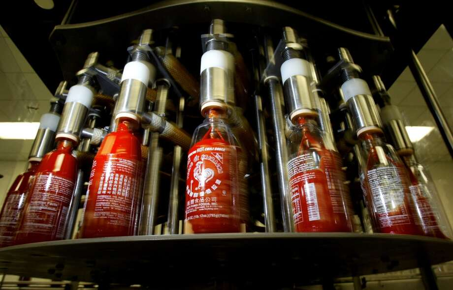 In this Jan. 28, 2005 photo, bottles of  Sriracha hot sauce are filled with product  at Huy Fong Foods Inc. in Rosemead, Calif. The city of Irwindale, where Huy Fong has a production facility, on Monday, Oct. 28, 2013 filed a lawsuit in Los Angeles Superior Court asking a judge to stop production at the factory, claiming the chili odor emanating from the plant is a public nuisance. (AP Photo/San Gabriel Valley Tribune, Greg Andersen) MAGS OUT; NO SALES; MANDATORY CREDIT Photo: Greg Andersen, Associated Press