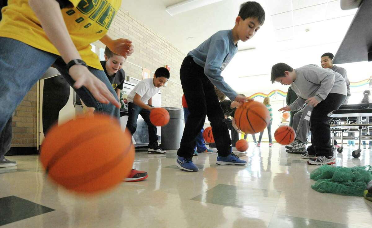 Michael Wolfe, background far right, a freshman on the Siena men's basketball team, times sixth graders as they dribble basketballs at Forts Ferry Elementary School during a visit by members of the Siena College basketball teams on Wednesday, Jan. 8, 2014, in Colonie, N.Y. (Paul Buckowski / Times Union)