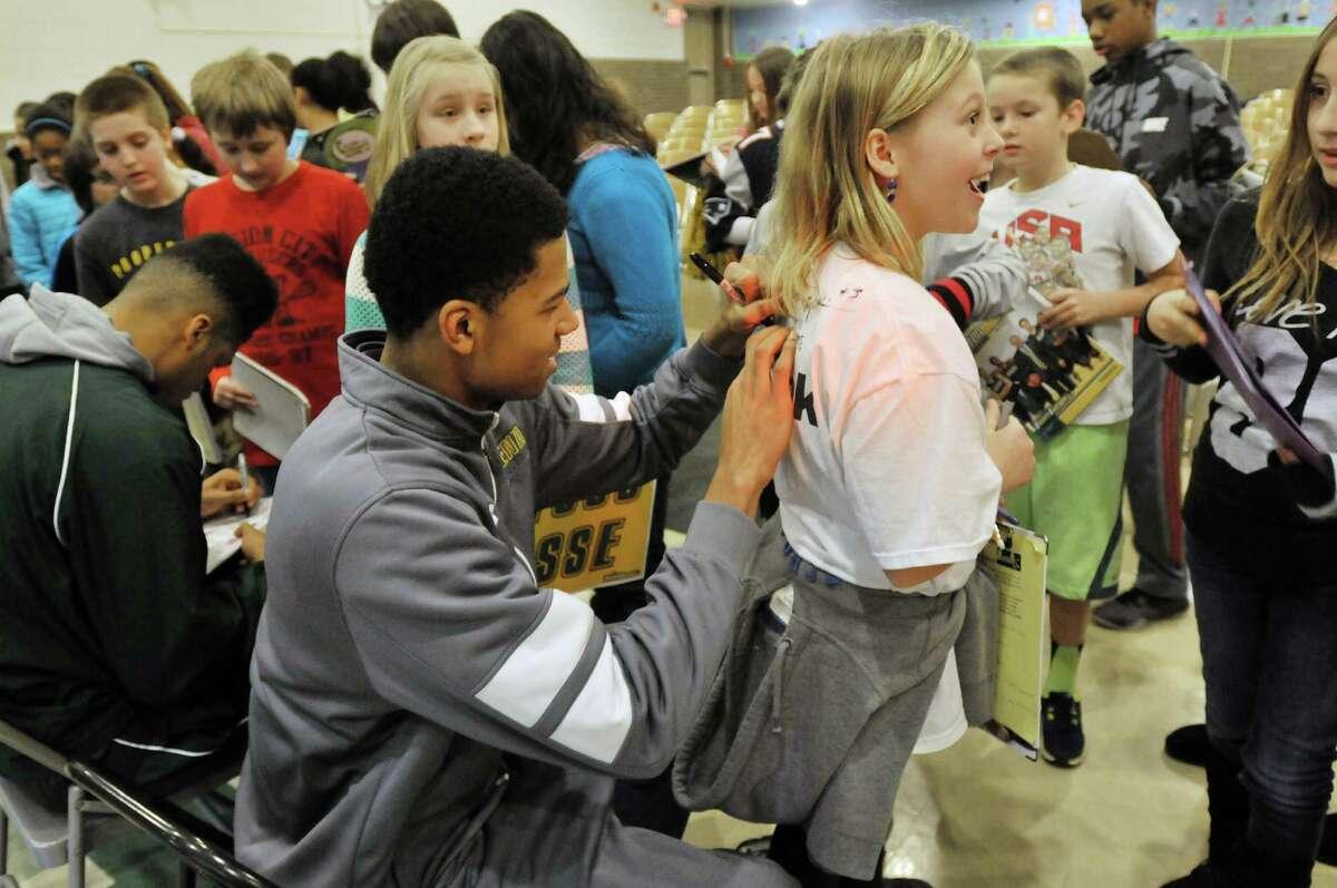 Michael Wolfe, left, a freshman on the Siena men's basketball team, signs the shirt of sixth grader Emelene Burek, 11, Wednesday, Jan. 8, 2014, at Forts Ferry Elementary School in Colonie, N.Y. (Paul Buckowski / Times Union)