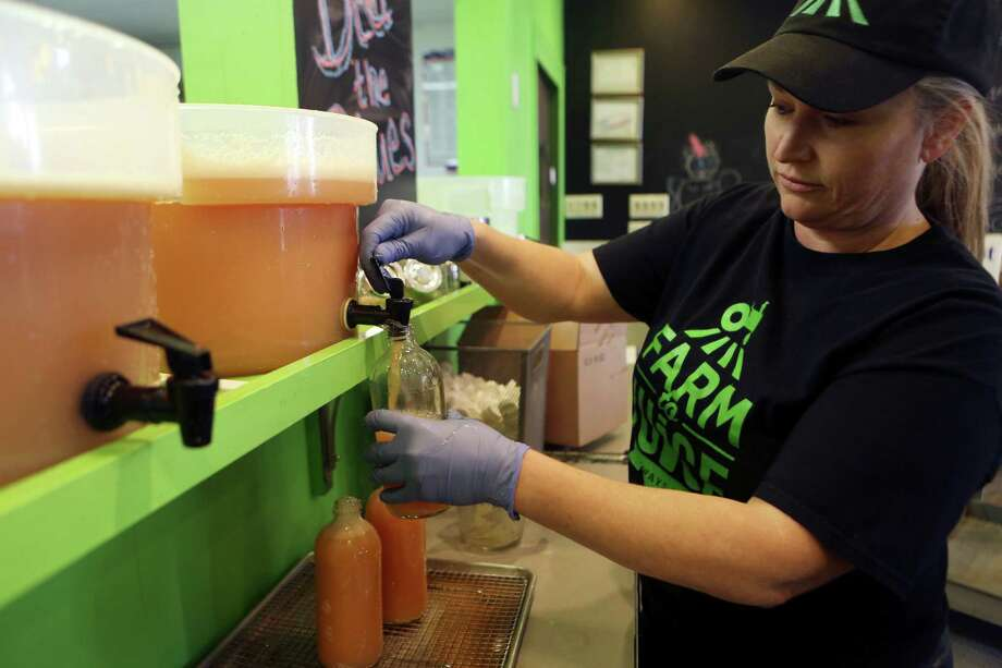 Lisa Baughn fills juice bottles on Monday Jan. 6, 2013 at Farm to Juice, a part of a growing number of juice cafes in San Antonio.  Baughn and her husband own the cafe. Photo: Helen L. Montoya, SAN ANTONIO EXPRESS-NEWS / SAN ANTONIO EXPRESS-NEWS