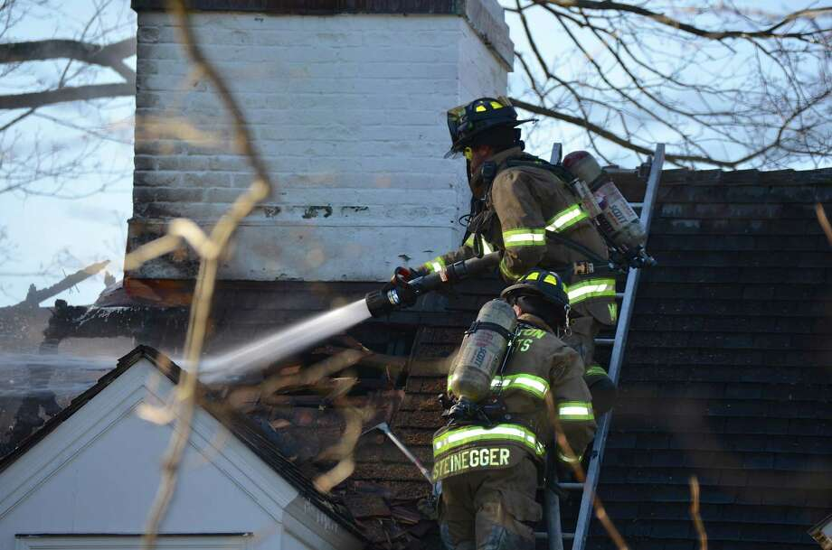 Darien and Noroton Heights firefighters responded to a structure fire at 261 Hollow Tree RIdge Road on Wednesday, Jan 8, 2014, in Darien, Conn. Photo: Jeanna Petersen Shepard / Darien News freelance Jeanna Petersen Shepard