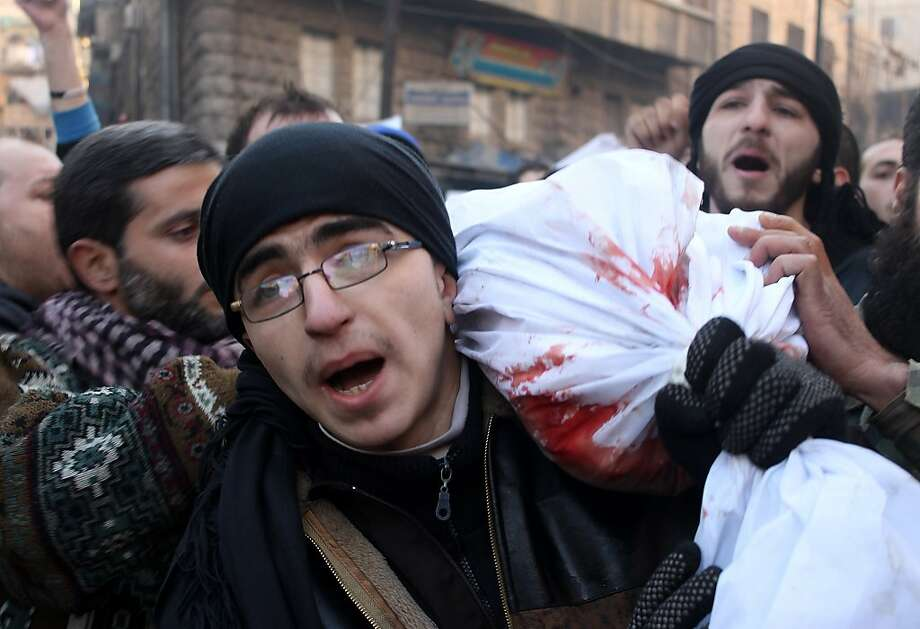 Mourners carry the body of a comrade killed during fighting with an al Qaeda group in the city of Aleppo. Photo: Mohammed Wesam, AFP/Getty Images
