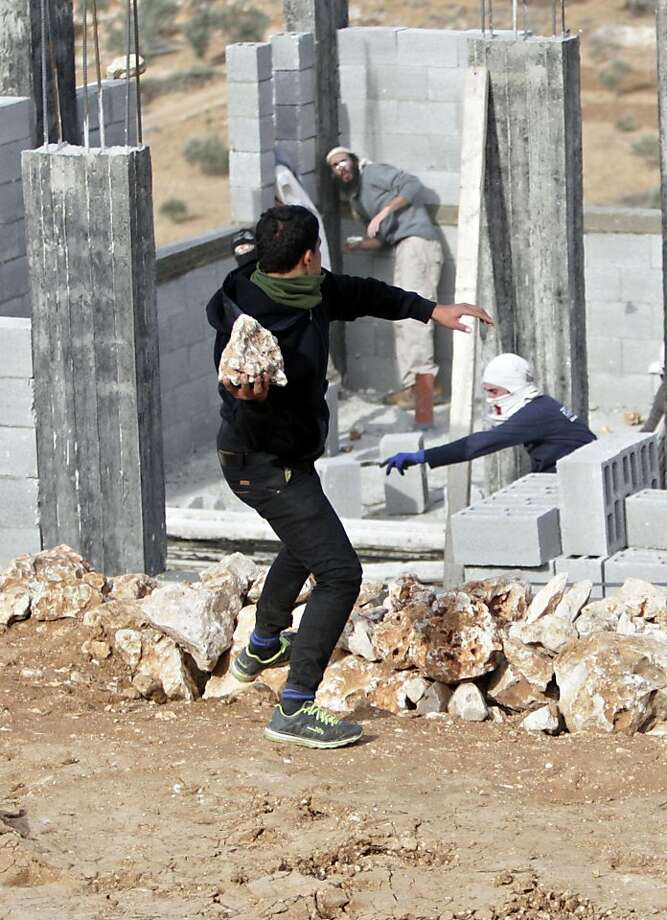 """Illegal settlers clash with Palestinians:A Palestinian youth throws a rock at Israeli settlers in a building under construction near the West Bank village of Qusra. Palestinians detained more than a dozen Israeli settlers for about two hours in retaliation for the latest in a string of settler attacks on villages in the area, witnesses said. The Israeli military said the chain of events apparently began after Israeli authorities removed an illegally built structure in Esh Kodesh, a rogue Israeli settlement in the area. In recent years, rogue settlers have often responded to Israeli military interference by attacking Palestinians and their property in a tactic known as """"price tag."""" Photo: Nasser Ishtayeh, Associated Press"""