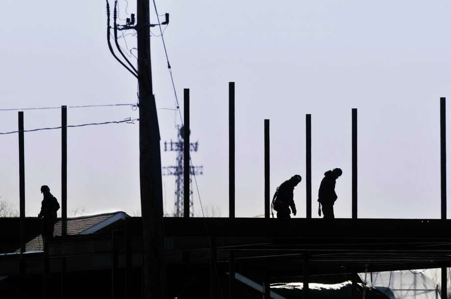 Construction workers battle the elements Wednesday, Jan. 8, 2014, while working on buildings in the Village of New Loudon development along Route 9 next to Hoffman's Playland, in Colonie, N.Y.  (Paul Buckowski / Times Union) Photo: Paul Buckowski