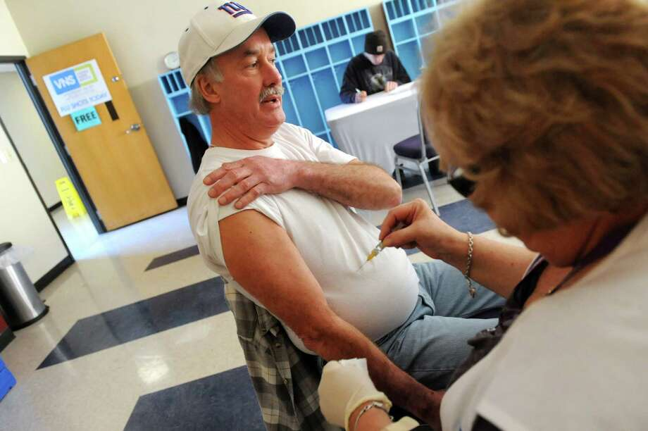 Tom Newell of Colonie, left, readies his arm for a flu shot from Diane Shagnon-Burns, a registered nurse with the Visiting Nurse Service of Northeastern New York during a free flu clinic on Wednesday, Jan. 8, 2014, at the North Albany YMCA in Albany, N.Y. (Cindy Schultz / Times Union) Photo: Cindy Schultz / 00025144A