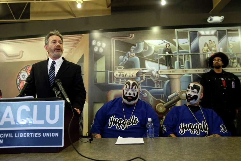 Michael J. Steinberg, legal director for the ACLU of Michigan addresses the media as Joseph Bruce aka Violent J, center, and Joseph Utsler aka Shaggy 2 Dope, members of the Insane Clown Posse listen in Detroit, Wednesday, Jan. 8, 2014. The rap metal group sued the U.S. Justice Department on Wednesday over a 2011 FBI report that describes the duo's devoted fans, the Juggalos, as a dangerous gang, saying the designation has tarnished their fans' reputations and hurt business. The American Civil Liberties Union filed the lawsuit in Detroit federal court on behalf of the group's two members. (AP Photo/Carlos Osorio) ORG XMIT: MICO105 Photo: Carlos Osorio / AP