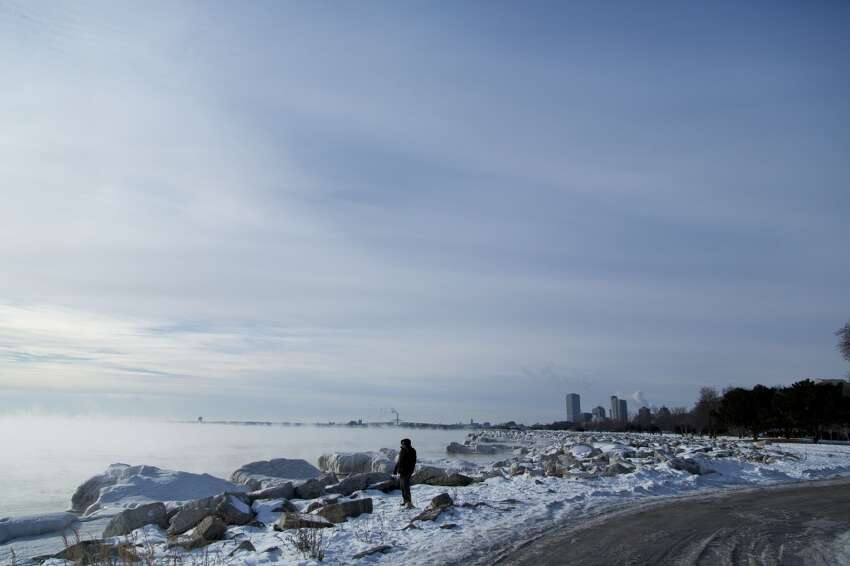 A man braves the cold and walks along the shore of Lake Michigan as temperatures remain in the negative digits on Jan. 7, 2014 in Milwaukee, Wis. A 'polar vortex' of frigid air centered on the North Pole dropped temperatures to the negative double digits at its worst. (Photo by Darren Hauck/Getty Images)