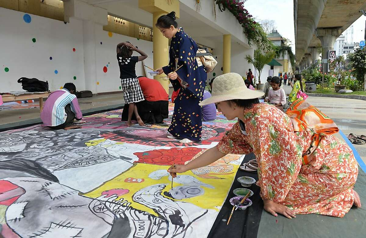 Indian street children, along with Japanese children from Fukushima, paint on a huge canvas during an art work titled