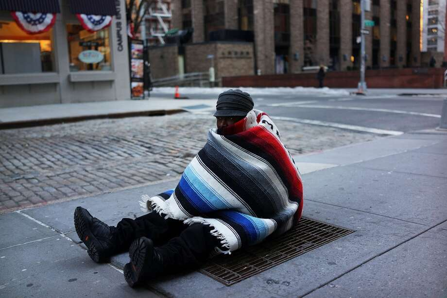 """Prince, who is homeless, sits on a subway grate to keep warm on a frigid day on Jan. 7, 2014 in New York. A """"polar vortex"""" carrying Arctic air and wind gusts of up to 50 mph has engulfed New York City and much of the Northeast making for life threatening weather conditions.  (Photo by Spencer Platt/Getty Images) Photo: Spencer Platt, Getty Images"""