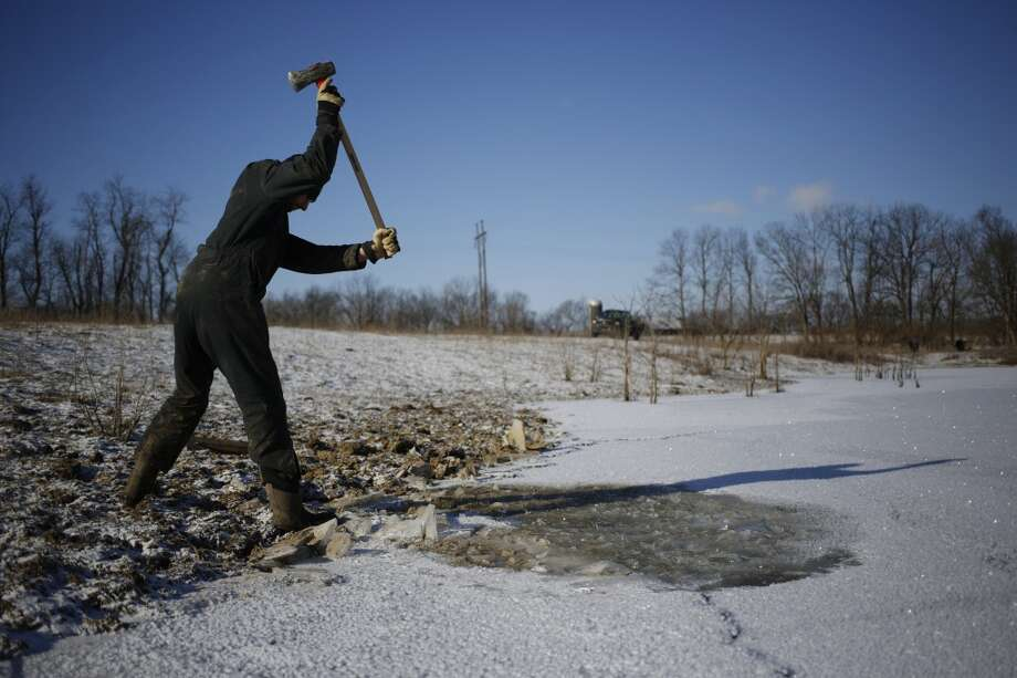 Organic farmer Will Muir of Wholesome Living Farm breaks through the ice on a pond so his cows can access drinking water in the midst of bitter cold below-zero temperatures on Jan. 7, 2014 in Kentucky. Temperatures in the single digits coupled with below-zero wind chills have prompted the closure of local governments, schools, and businesses throughout the South. (Photo by Luke Sharrett/Getty Images) Photo: Luke Sharrett, Getty Images