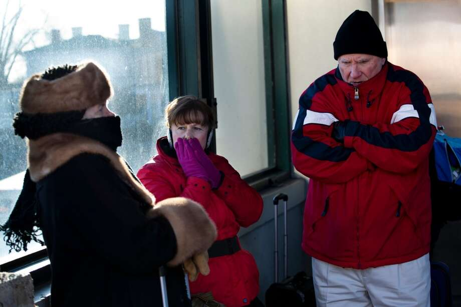 Cecile Folan, left, Karen Higbie, center, and her husband Warren Higbie, right, try to keep warm while waiting for the train at the train station in downtown Fredericksburg, Va on Tuesday, Jan. 7, 2013. The Polar Vortex that has gripped much of the nation brought temperatures into the single digits in the Fredericksburg area today. (AP Photo/The Free Lance-Star, Autumn Perry) Photo: Autumn Parry, Associated Press