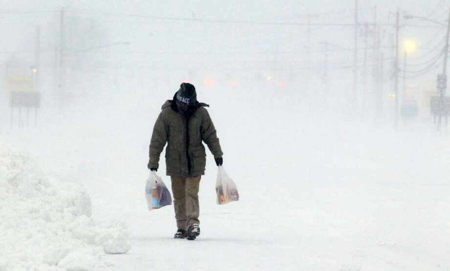 Lucas Hunter from Pittsburgh, walks to his hotel along Camp Road in Hamburg, N.Y. after a stretch of the New York State thruway  was closed down due to high winds Tuesday, Jan. 7, 2014. (AP Photo/The Buffalo News, Harry Scull Jr.) Photo: HARRY SCULL JR, Associated Press